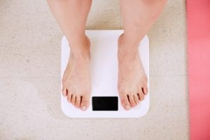 person weighing herself with scale